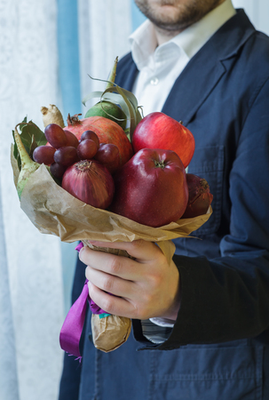 unusual vegetables: Man gives unusual bouquet of fresh fruits and vegetables.