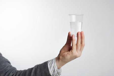 vasos de agua: Hombre que sostiene un vaso de plástico desechable con agua. Foto de archivo