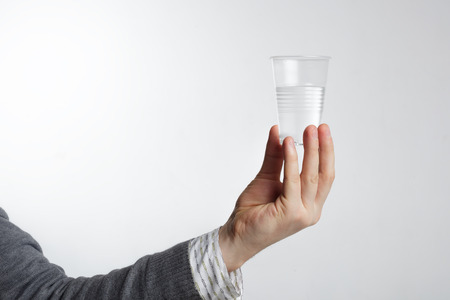 cup of water: Man holding a disposable plastic cup with water. Stock Photo