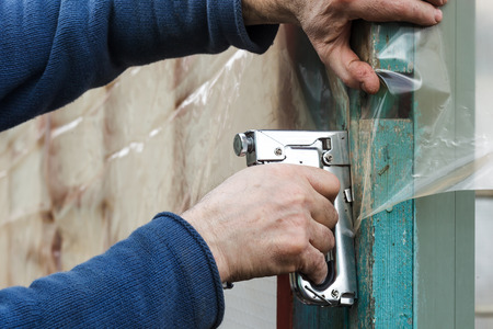 polyethylene film: builder fixes polyethylene film with staple gun
