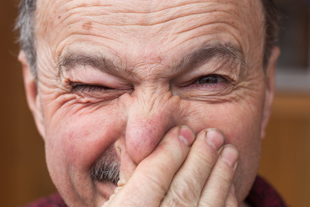 unpleasant smell: Elderly man hands nose plugs because of unpleasant smell