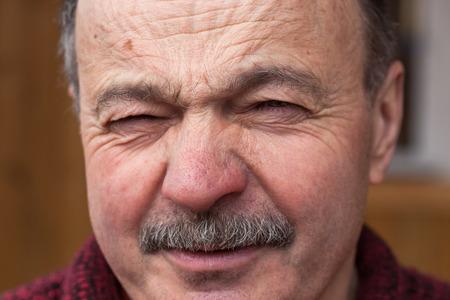 desconfianza: Hombre mayor con desprecio mirando a la cámara, arruga la nariz y la frente