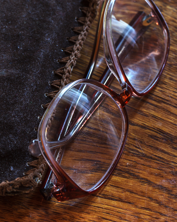 blurred vision: Old pensioner glasses on lacquered wooden surface. Blurred vision of old age