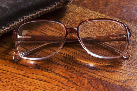gafas de pensionista en superficie de madera lacada. visión borrosa de la vejez Foto de archivo