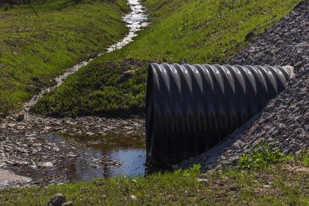 sewer: huge black plastic sewer and small stream Stock Photo