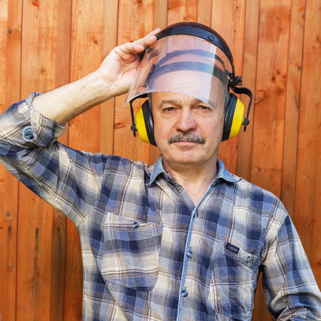 resting mask: Senior builder in protective mask and headphones resting during a break Stock Photo