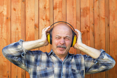 unpleasant: elderly man in a protective building headphones. Unpleasant sounds during construction