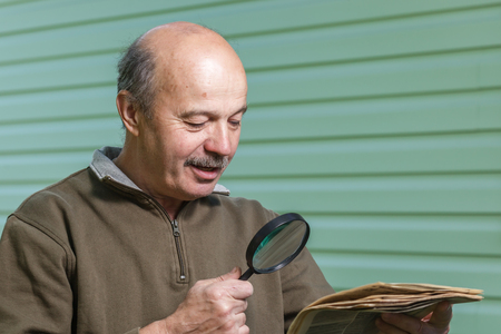 vision problems: Pensioner reads ad in the newspaper, looking through a magnifying glass. vision problems in old age