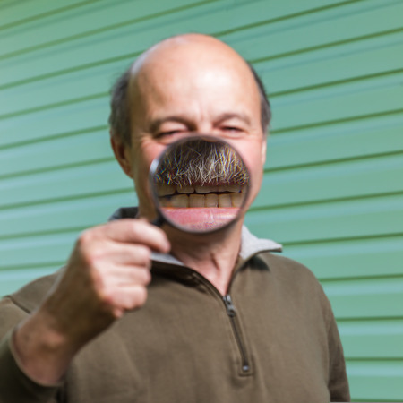 incorrectly: Elderly ranger incorrectly uses a magnifying glass because of forgetfulness. The increase in the teeth and mouth with a magnifying glass: tomfoolery and stupidity Stock Photo