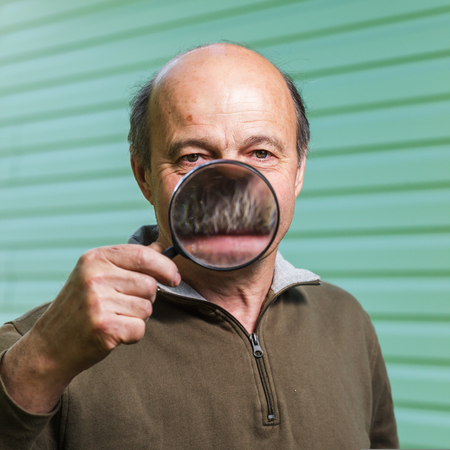 stupidity: Elderly ranger incorrectly uses a magnifying glass because of forgetfulness. The increase in the teeth and mouth with a magnifying glass: tomfoolery and stupidity Stock Photo