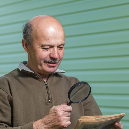 hyperopia: Pensioner reads ad in the newspaper, looking through a magnifying glass. vision problems in old age