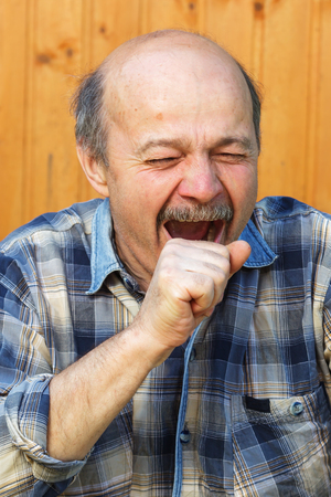 exhaustion: Elderly man yawns from exhaustion. Farmer resting in nature Stock Photo