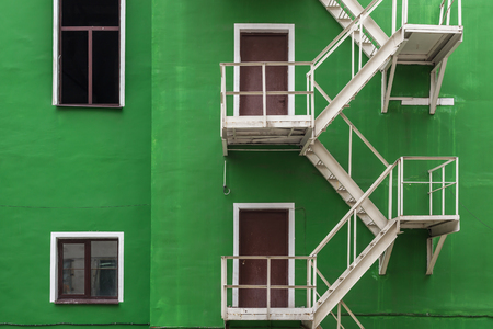 emergency stair: exterior staircase on green wall of a building. Modern architecture Stock Photo