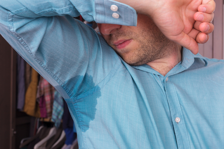 worries: Sweaty spot on the shirt because of the heat, worries and diffidence Stock Photo