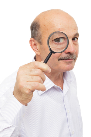 Man scientist looks at something through a magnifying glass