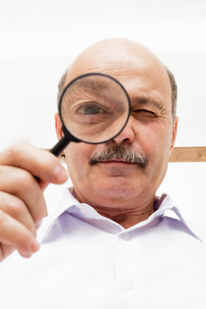 looking through an object: Man scientist looks at something through a magnifying glass