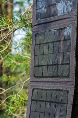 accumulate: Portable solar panels are hanging on a tree and accumulate energy Stock Photo