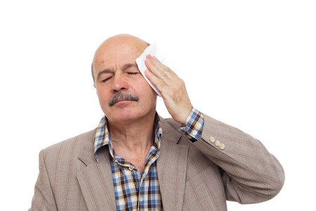 Elderly and the sick man wipes the sweat from his forehead. To be ill during the heat. Stock Photo