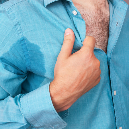 perspiration: Sweaty armpit and a wet spot on his shirt because of the heat Stock Photo