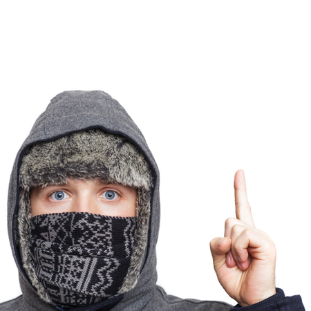Young man in hat, scarf and hood hiding from the cold weather in the winter on a white background