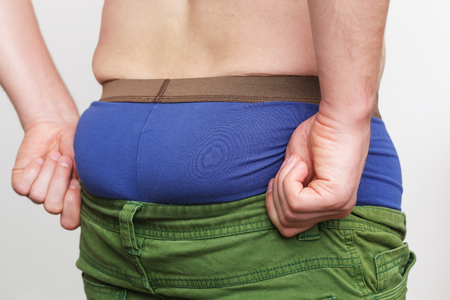 man ass: Weight gain due to improper diet. Fatty side and small pants Stock Photo