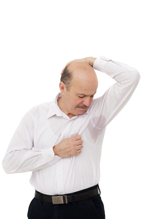 hyperhidrosis: Old man in horror looking at the sweaty shirt. Sweaty spot on the shirt because of the heat, worries and diffidence