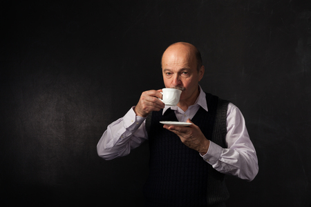 sip: elderly bald man with a mustache takes a sip of coffee from a white mug.