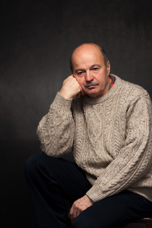 rooting: elderly man sits and looks thoughtfully, pondering problem or complex issue in sweater.