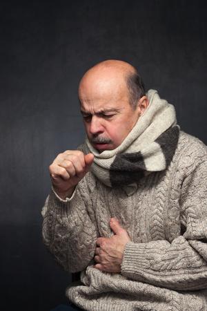 Bejaarde man is ziek van verkoudheid of longontsteking. oudere man in een trui en een wollen sjaal sterk hoest