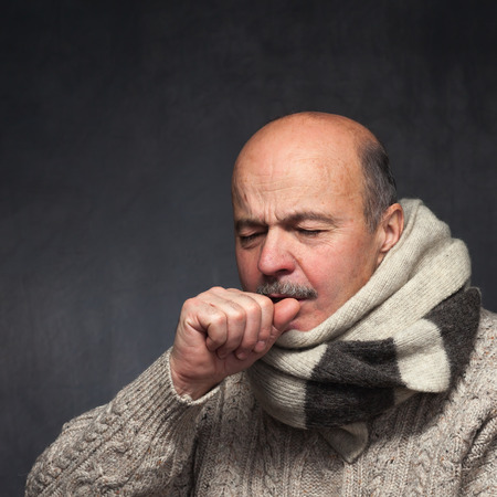 strongly: Elderly man is ill from colds or pneumonia. elderly man in a sweater and a woolen scarf strongly coughs Stock Photo