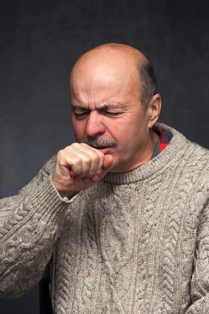 Elderly man is ill from colds or pneumonia. elderly man in a sweater and a woolen scarf strongly coughs Stockfoto