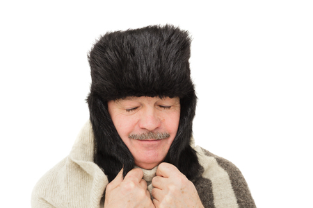 flaps: elderly man in fur hat with ear flaps covers his ears from the cold and eyes.
