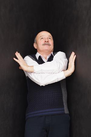 Elderly man pushes black walls.