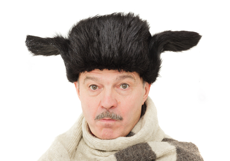 elderly man in a fur hat disappointed: puffed cheeks and sad look.