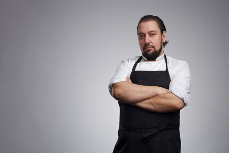 Chef cook in white uniform and a black apron, he folded his arms and looking confidently forward