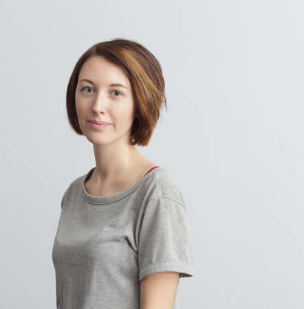 confidently: Girl with short red hair in a gray T-shirt calmly and confidently looking at the camera.