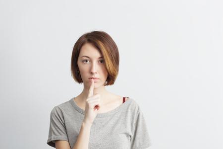 guardar silencio: Guardar silencio o secreto. La muchacha pone el dedo en los labios