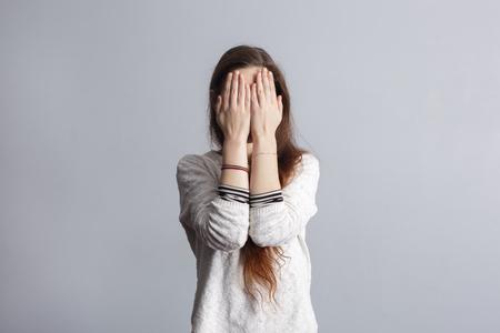 Meisje met lang haar heeft betrekking op zijn gezicht met zijn handen. Depressie en eenzaamheid bij jongeren. Stockfoto