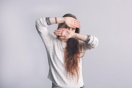 Chica con el pelo largo cubre la cara con las manos. La depresión y la soledad en la juventud.