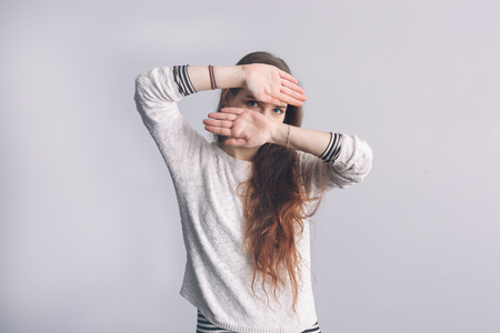 bashful: Girl with long hair covers his face with his hands. Depression and loneliness in youth. Stock Photo
