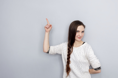 attract attention: Girl with long hair shows index finger up, attracting attention Stock Photo