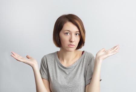 disagreeing: Girl puzzled shrugs, misunderstanding and disagreeing. Stock Photo