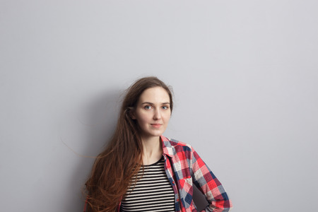 red plaid: Girl in a red plaid shirt standing near the wall and looking confidently forward