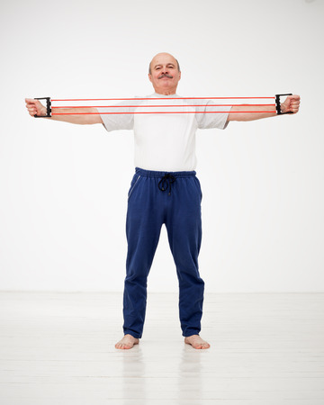 strengthen: Elderly man goes in for sports with the exerciser expander. Exercise to strengthen muscles