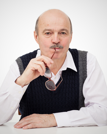 Elderly bald man with a mustache sitting at the table and eats eyeglasses. Stupid habit of taking things in his mouth.