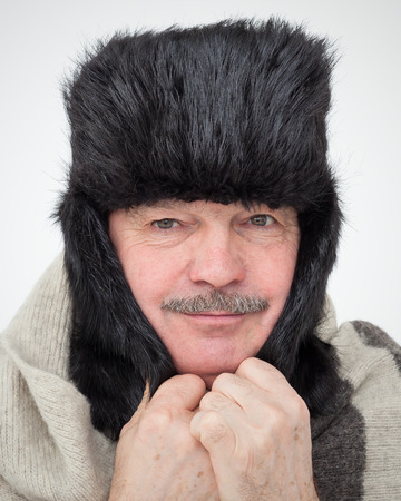 unfavorable: Elderly man bundled up in fur hat and warm scarf. Very cold winter and unfavorable weather forecast.