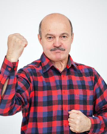 stubbornness: Elderly bald man with a mustache shows his hand with his fists. The call to action and a show of force. Stock Photo