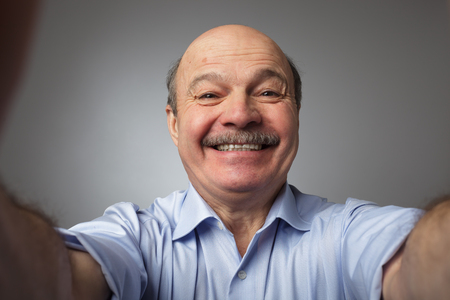 broadly: Elderly man with a mustache holding a smartphone and makes selfie, smiling broadly