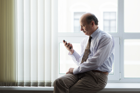 read news: Elderly man sitting on a windowsill and read news on your smart-phone. Rest in the middle of the working day.