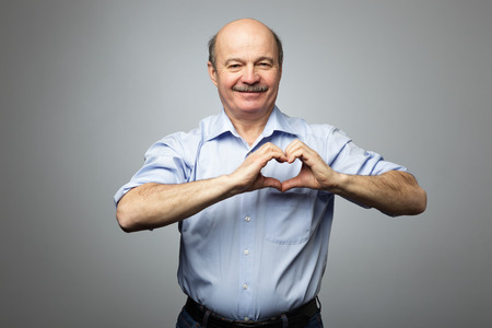 old man making out of hands heart. Doing charity work, take care of the health, or being in love